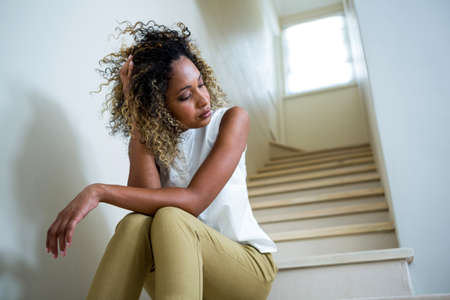 tensed: Tensed woman sitting on stairs LANG_EVOIMAGES
