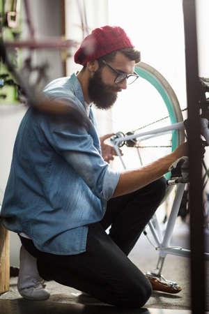 repair shop: Bike mechanic repairing a bicycle in bike repair shop