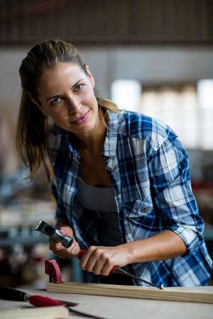 carpenter's bench: Portrait of female carpenter using chisel on wooden plank in workshop