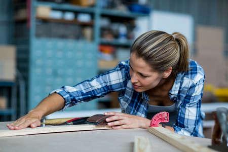 rubbing: Female carpenter rubbing wooden plank with sanding block in workshop LANG_EVOIMAGES