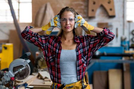 muff: Portrait of female carpenter holding ear muff in workshop