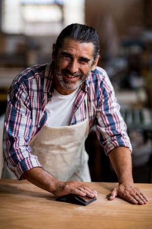 sanding block: Portrait of carpenter rubbing wood with sanding block in workshop