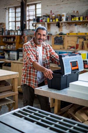 competencias laborales: Retrato de carpintero de pie con la caja de herramientas en el taller LANG_EVOIMAGES