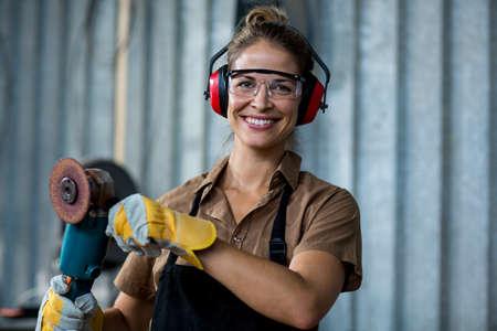 muff: Female carpenter holding a polishing machine in workshop
