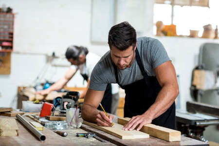carpenter's bench: Carpenter marking on wooden plank with pencil in workshop LANG_EVOIMAGES