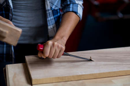 workwoman: Mid section of female carpenter using mallet and chisel in workshop