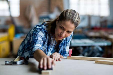 sanding block: Female carpenter rubbing wooden plank with sanding block in workshop LANG_EVOIMAGES
