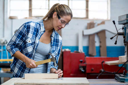 workwoman: Female carpenter holding a hammer to drive nail into a wooden plank in workshop
