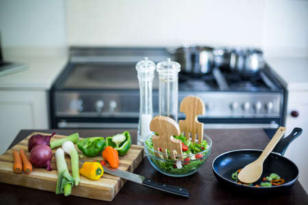 worktop: Bowl of salad, vegetables and pan on kitchen worktop at home LANG_EVOIMAGES