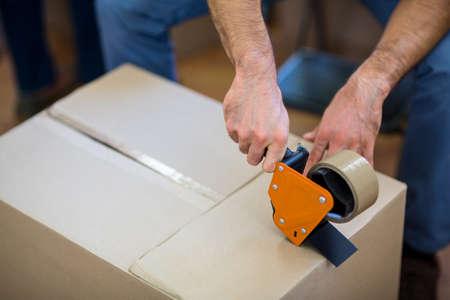 sealing tape: Close-up of man sealing a cardboard box