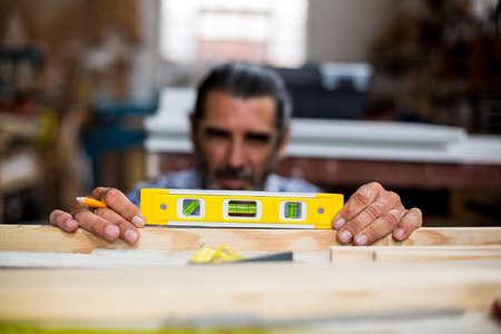 carpenter's bench: Carpenter measuring a length of wooden plank with spirit level in workshop