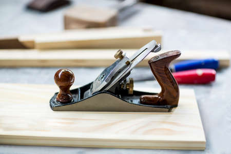 plane table: Wooden plank and jack plane on table in workshop