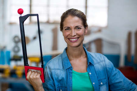 coping: Portrait of happy female carpenter holding coping saw in workshop LANG_EVOIMAGES