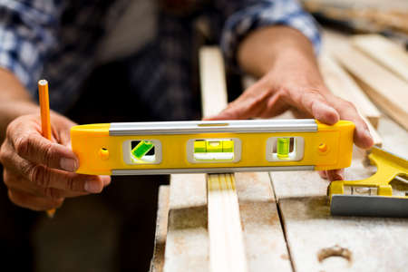 spirit level: Carpenter measuring a length of wooden plank with spirit level in workshop
