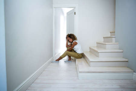 tensed: Tensed woman sitting on stairs at home LANG_EVOIMAGES
