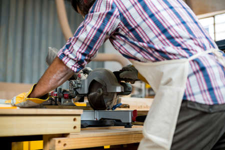 electric saw: Mid section of carpenter cutting wooden plank with electric saw in workshop LANG_EVOIMAGES