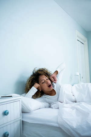 waking: Woman waking up in bed at morning LANG_EVOIMAGES