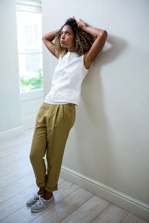 tensed: Tensed woman leaning on wall at home LANG_EVOIMAGES