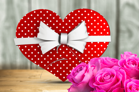 candy box: Heart shaped box of candy against a wall