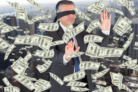blindfold: Mature businessman in a blindfold against view of cityscape Stock Photo