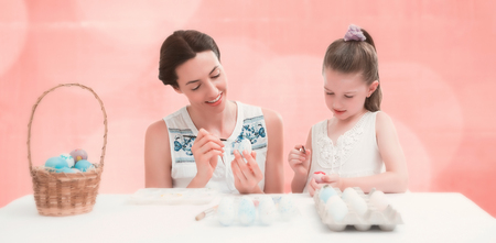 acclamation: Mother and daughter painting easter eggs against background of colors Stock Photo