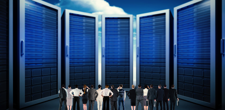 server side: Rear view of multiethnic business people standing side by side against composite image of server room Stock Photo