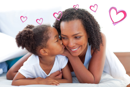 endearment: Red Hearts against cute little girl woman kissing her mother lying down on bed Stock Photo