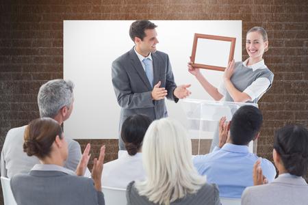 Receiving: Business people receiving award against a dark wall