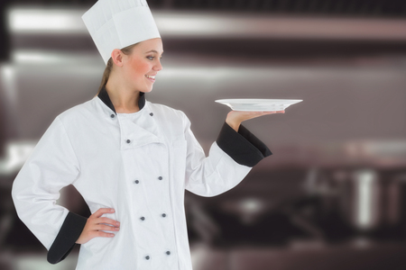 stove top: Female chef looking at plate against pots and pans on stove top