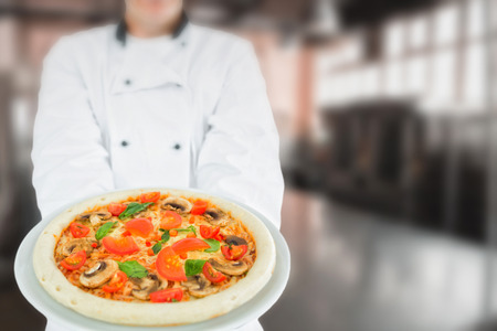 with no one: Chef holding delicious pizza against no one in the room Stock Photo