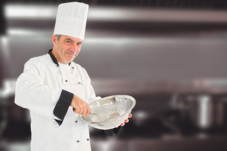 stove top: Mature chef using whisk and mixing bowl against pots and pans on stove top