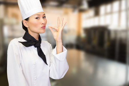 with no one: Smiling female cook in the kitchen against no one in the room Stock Photo