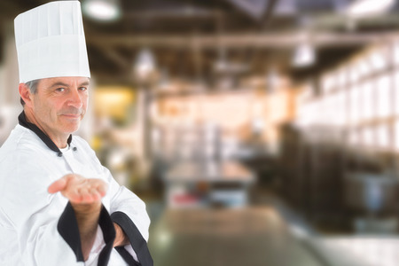 with no one: Male chef presenting an invisible product  against no one in the room
