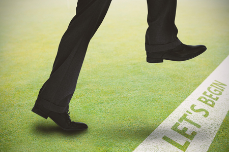 stepping: Businessman stepping against grassy landscape