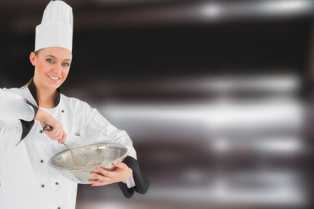 wire whisk: Happy female chef holding wire whisk and mixing bowl against deep fat fryers