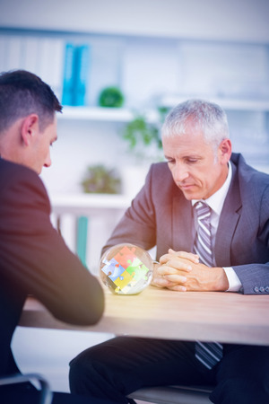clairvoyant: Colorful jigsaw pieces against two businessmen watching crystal ball
