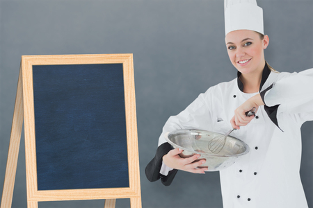 mixing board: Happy female chef holding wire whisk and mixing bowl against a board in a white background