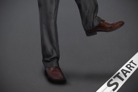 stepping: Businessman stepping against grey Stock Photo