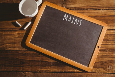 mains: Mains message  against chalkboard on desk Stock Photo