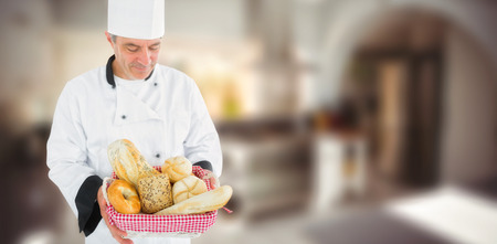composite image: Composite image of friendly chef holding a bread basket  on a blurred background