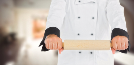 rolling up: Close up on a chef holding a rolling pin  against kitchen in a stylish home
