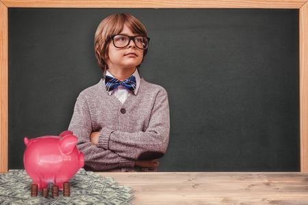 to make believe: Cute pupil dressed up as teacher against coins and piggy bank