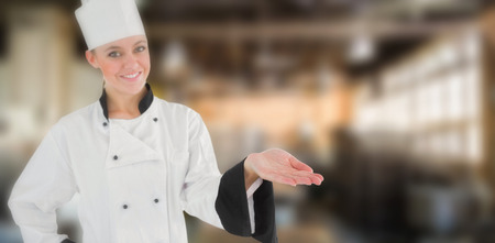 with no one: Portrait of a woman chef holding out her hand against no one in the room
