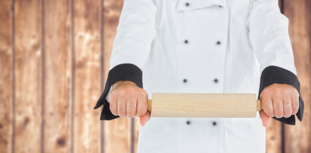 rolling up: Close up on a chef holding a rolling pin  against wooden planks background