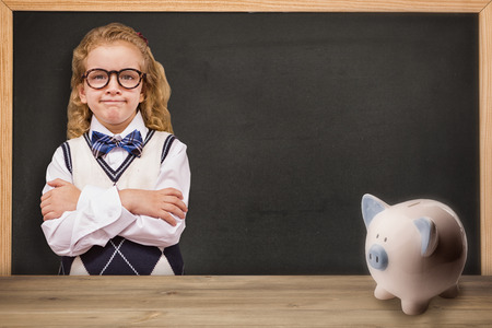 rear view girl: Cute pupil with arms crossed against piggy bank