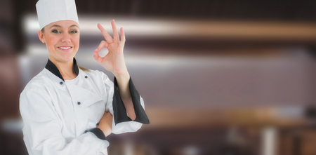 stove top: Happy female chef gesturing ok sign  against pots and pans on stove top Stock Photo