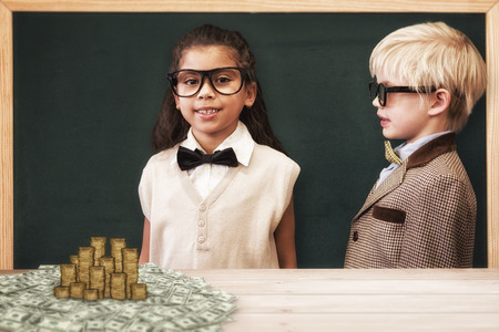 pupils: Cute pupils dressed up as teachers against gold coins Stock Photo