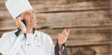 composite image: Composite image of chef calling on the phone on a wooden background Stock Photo