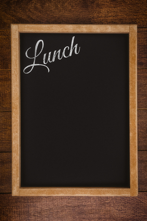 garnishing: Lunch message on a white background against a black board is posing on a wall