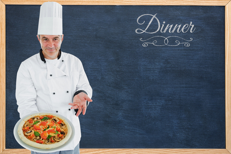 whites: Chef displaying delicious pizza against dinner message on a white background Stock Photo